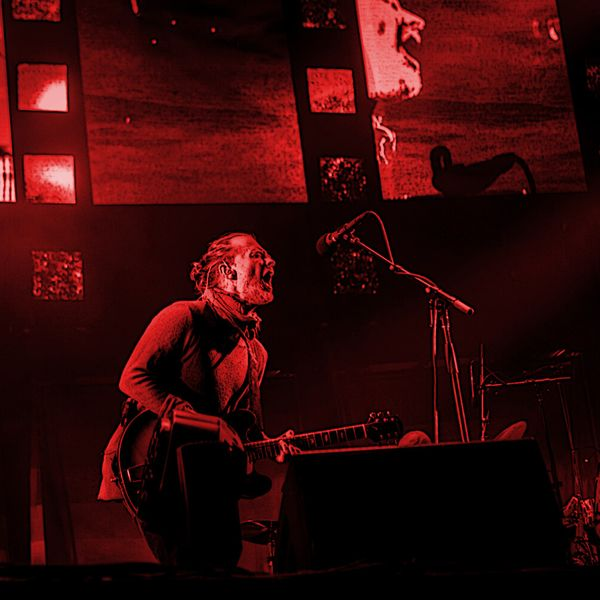Stained red photograph of Thom Yorke performing onstage
